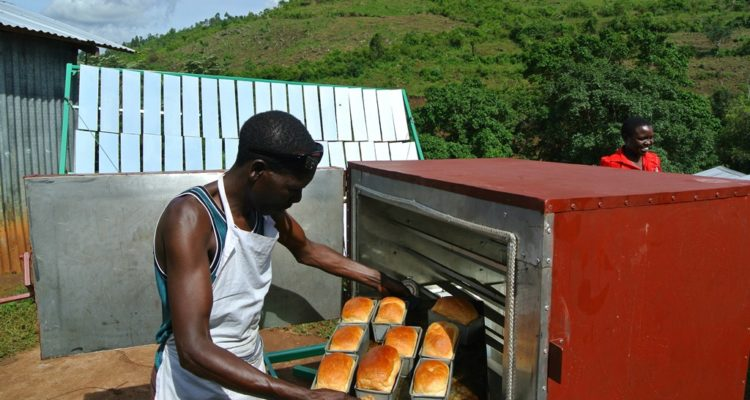 A Kenyan baker at the Koptigei Cooperative pulling out freshly baked bread from a solar-reliant oven